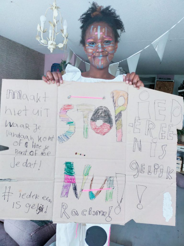 meisje met 'stop racisme' protestbord